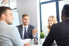 Business people in discussing something while sitting together at the table. Business people in discussing something while sitting together at the table Stock Photography