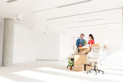 Business people discussing while standing by cardboard boxes in new office Stock Photography