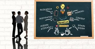 Business people discussing while standing by innovation diagram on blackboard Royalty Free Stock Photos
