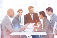 Business people disscussing a budget plan. Business team showing ethnic diversity in a meeting smiling at the camera Royalty Free Stock Photo