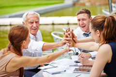 Business people doing high five in a meeting Stock Photo