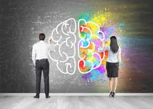 Business people drawing brain on chalkboard. Rear view of a businessman and a businesswoman drawing a colorful large brain sketch on a blackboard. Concept of Stock Photos