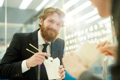 Business people Eating Chinese food in office. Portrait of modern bearded businessman smiling happily while eating Chinese food in office sharing lunch with royalty free stock photos