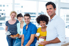 Business people eating donuts and drinking Royalty Free Stock Photos