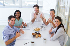 Business people eating muffins give thumbs up to camera Royalty Free Stock Image
