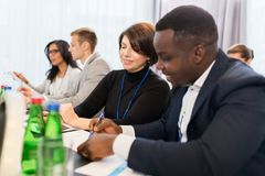 Business team at international conference. Business, people and education concept - businessman and businesswoman at conference discussing papers Royalty Free Stock Photo