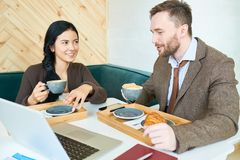 Business People Enjoying Conversation in Cafe royalty free stock images