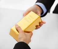 Business people exchanging golden bar Stock Photography