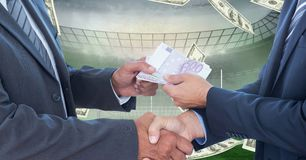 Business people exchanging money at football stadium representing corruption Stock Photography