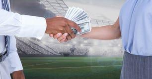 Business people exchanging money at stadium. Digital composite of Business people exchanging money at stadium stock photography