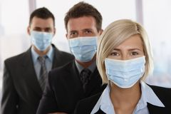 Business people fearing h1n1 virus. Business people fearing h1n1 swine flu virus wearing protective face mask and standing in a row Royalty Free Stock Images
