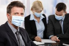 Business people fearing h1n1 virus. Businessman fearing h1n1 swine flu virus wearing protective face mask during meeting at office Stock Photos