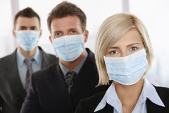 Business people fearing h1n1 virus. Business people fearing h1n1 swine flu virus wearing protective face mask and standing in a row Stock Photo