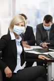 Business people fearing h1n1 virus. Businesswoman fearing h1n1 swine flu virus wearing protective face mask during meeting at office Stock Photos