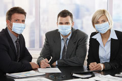 Business people fearing h1n1 virus. Business people fearing h1n1 swine flu virus wearing protective face mask during meeting at office Stock Image