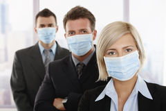 Business people fearing h1n1 virus. Business people fearing h1n1 swine flu virus wearing protective face mask and standing in a row Stock Images