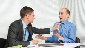 Business people fighting. At the desk in office Royalty Free Stock Photography