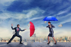 Business people fighting. Business people are fighting with umbrellas on the roof Royalty Free Stock Image