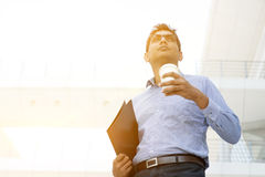 Business people, file folder and hot coffee cup. Asian Indian business man hand holding take away hot coffee cup and file folder in morning sunlight, outdoors Royalty Free Stock Photography
