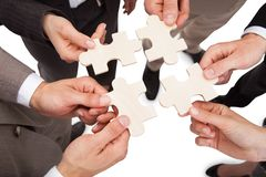 Business people fixing jigsaw pieces Royalty Free Stock Photo