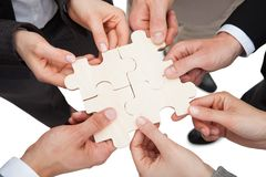 Business people fixing jigsaw pieces. High angle view of business people fixing jigsaw pieces over white background Stock Image