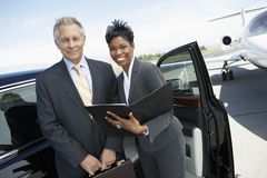 Business People With Folder At Airfield. Portrait of a happy businessman and businesswoman at airport Stock Images