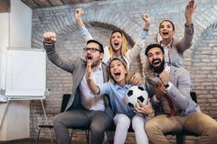 Business people or football fans watching soccer on tv and celebrating victory. Friendship, sports and entertainment concept. Happy business people or football stock photography