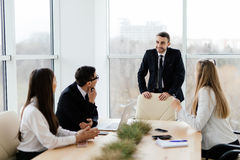 Business people in formalwear discussing with leader something while sitting together at the table Stock Photos