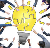 Business People Forming a Light Bulb Puzzle.  Stock Images
