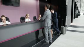 Business people at front desk stock footage