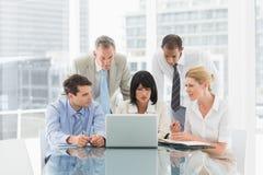 Business people gathered around laptop talking Stock Image