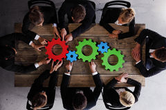 Business people gathering cogs stock images