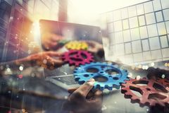 Business people with gears in hand that exit from a laptop. concept of remote cooperation and teamwork. Double exposure. Business people with gears in hand that stock image
