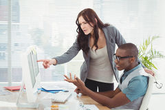 Business people gesturing while looking at computer Royalty Free Stock Image