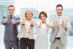 Business people gesturing thumbs up in office Stock Image