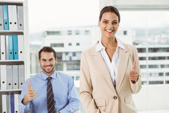 Business people gesturing thumbs up in office Royalty Free Stock Images