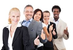 Business people gesturing thumbsup over white background Stock Image