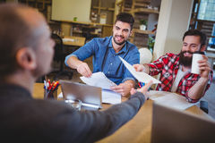 Business people giving documents to colleague Stock Photos