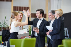 Business people giving high five. Successful team of business people giving high five in the office Stock Photo