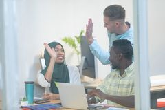 Business people giving high five while working together at desk in a modern office. Front view of diverse business people giving high five while working together royalty free stock photography