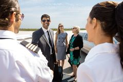Business People Greeting Pilot And Airhostess At Stock Photography