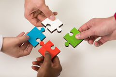Business people group assembling jigsaw puzzle and represent team support. And help concept, top view perspective at modern bright office interior Royalty Free Stock Photography