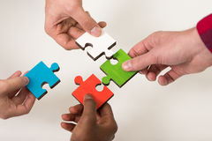 Business people group assembling jigsaw puzzle and represent team support Stock Image