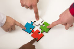 Business people group assembling jigsaw puzzle and represent team support Stock Photo