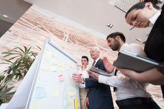 Business people group brainstorming and taking notes to flipboar Royalty Free Stock Photo