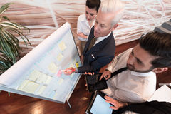 business people group brainstorming and taking notes to flipboard royalty free stock photography