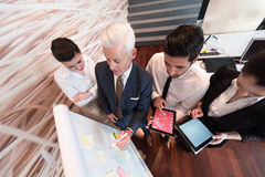 Business people group brainstorming and taking notes to flipboard Royalty Free Stock Image