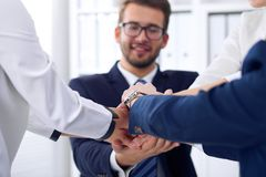 Business people group happy showing teamwork and joining hands or giving five after signing agreement or contract in Stock Photos
