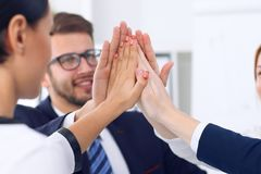 Business people group happy showing teamwork and joining hands or giving five after signing agreement or contract in Stock Photography