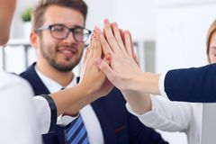 Business people group happy showing teamwork and joining hands or giving five after signing agreement or contract in Stock Images